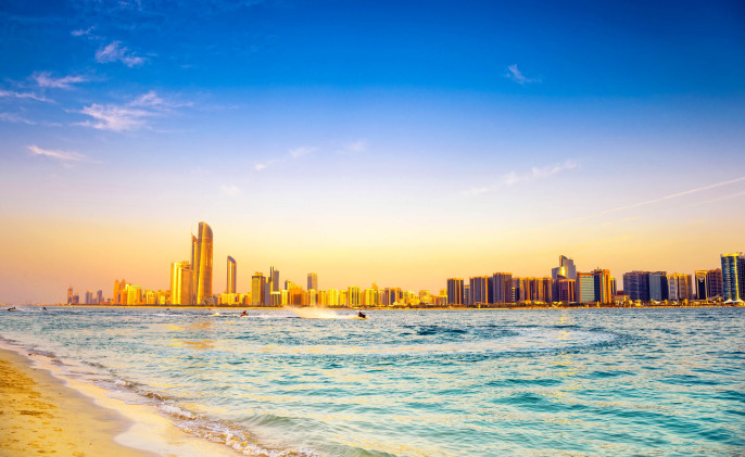 Beach with backdrop of Abu Dhabi skyline at sunset VAE iStock_000022783355_Large-2