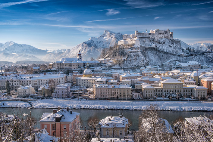 Unique panoramic shot of Salzburg with the famous Hohensalzburg Festung covered in fresh Snow. Beautiful Austrian Alps Backdrop.
