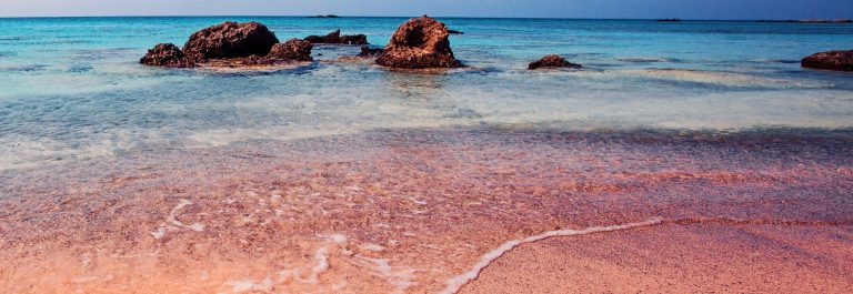 Crete, Greece. The Wave of the Sea on the Pink Sand on Beautiful Beach. Pink Sand Beach of Famous Crete Island Elafonisi (or Elafonissi)