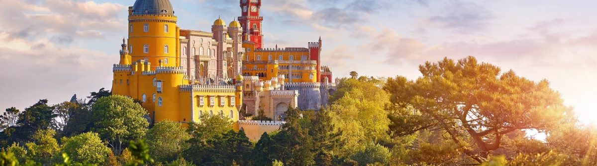 National-Palace-of-Pena-in-Sintra-near-Lisbon-Portugal.-Picturesque-landscape-with-dawn-and-green-trees.-Blue-morning-sky-with-clouds.-Image-shutterstock_1111720499_1920x1280